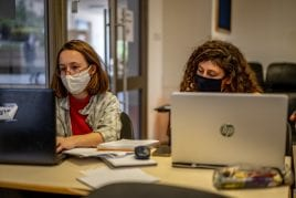 women with masks studying on laptops