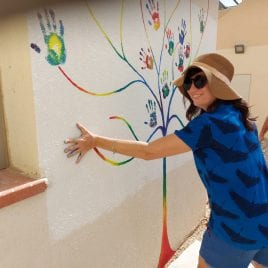 women imprinting her hand on wall mural